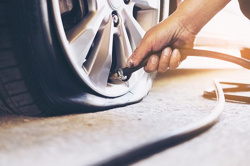 Technician is repairing car flat tire